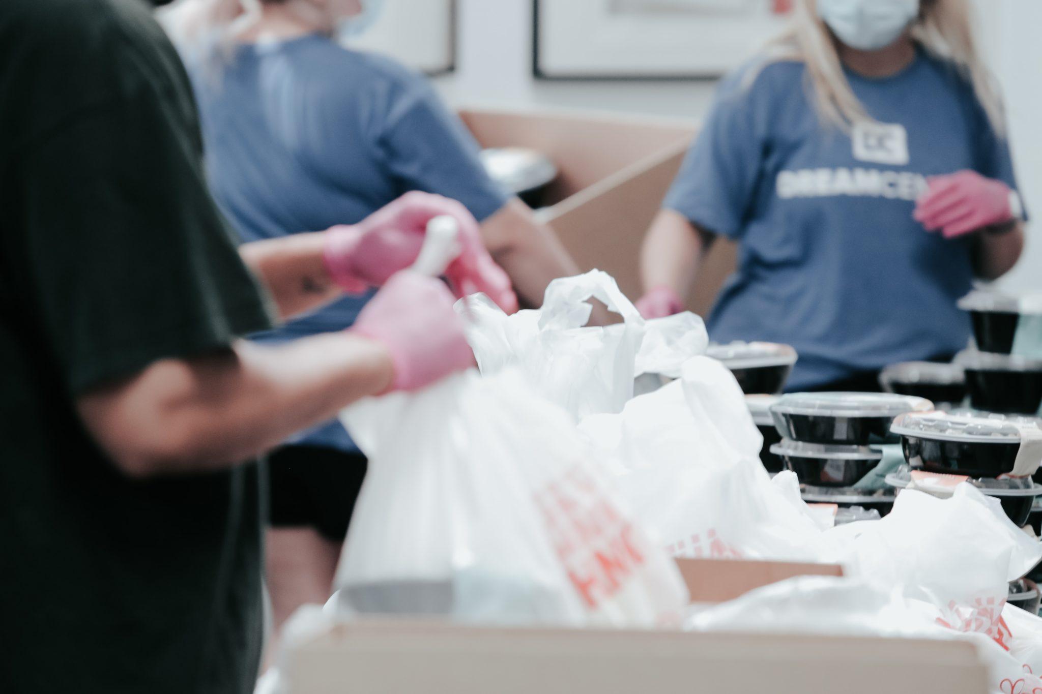 Pictures of volunteers packaging food